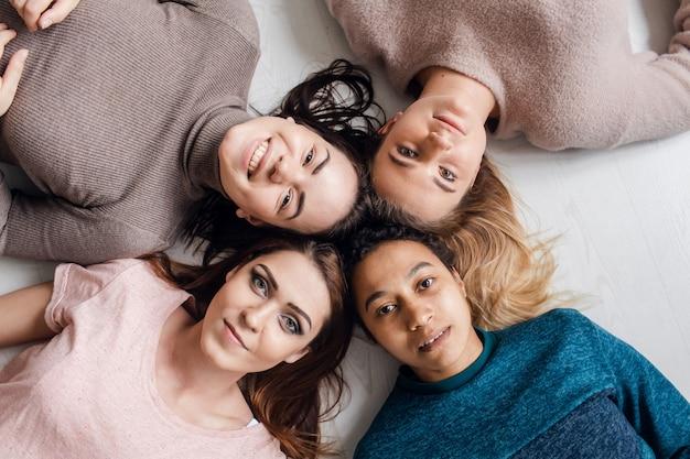 サークルに横たわっている4つの幸せな多様な民族のかなり若い女の子の女性の友人が一緒にカメラを見て、寝坊パーティーと多民族の友情の概念、上面図の肖像画