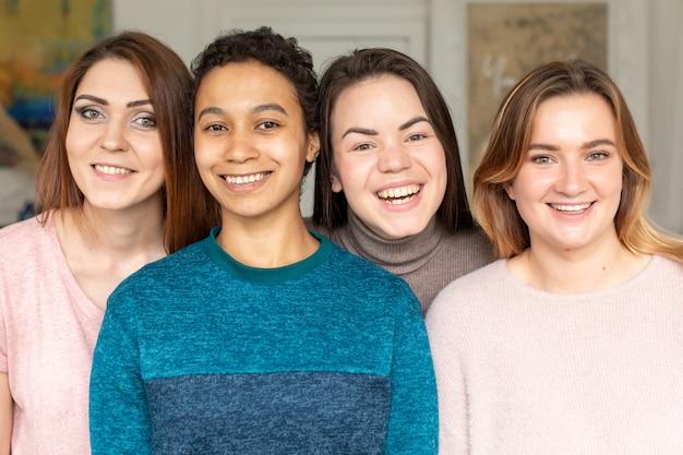 4つの幸せな多様な民族のかなり若い女の子の女性の友人が一緒に輪になっている、外泊パーティーと多民族の友情の概念、上面図の肖像画。