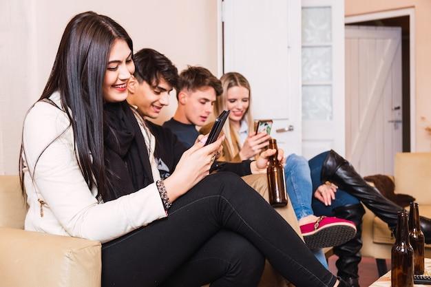 Четыре счастливых друга используют свои мобильные телефоны, сидя на диване дома. счастливые друзья сидят вместе, но все смотрят на свои смартфоны и пьют пиво.