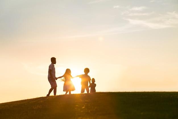 4人の幸せな子供たちが日没で遊んでいます彼らはジャンプして手で持っています
