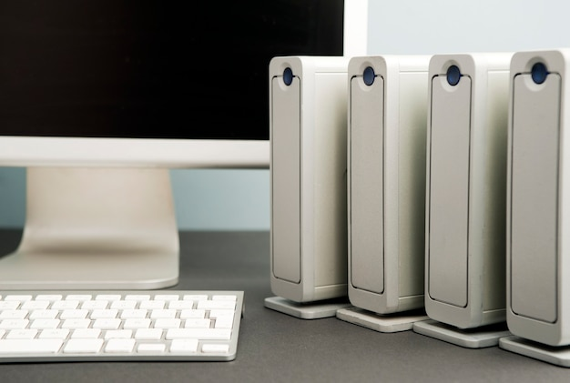 コンピューターのモニターとキーボードの部分ビューを備えた4台のハードドライブ。灰色青黒のテーブルの背景