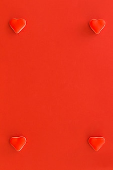 Four heart shape candies at the corner of red background