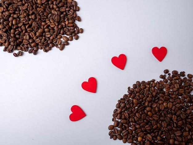 네 개의 하트가 흰색 밝은 배경에 떨어져있는 커피 콩 두 힙 사이에 놓여 있습니다.