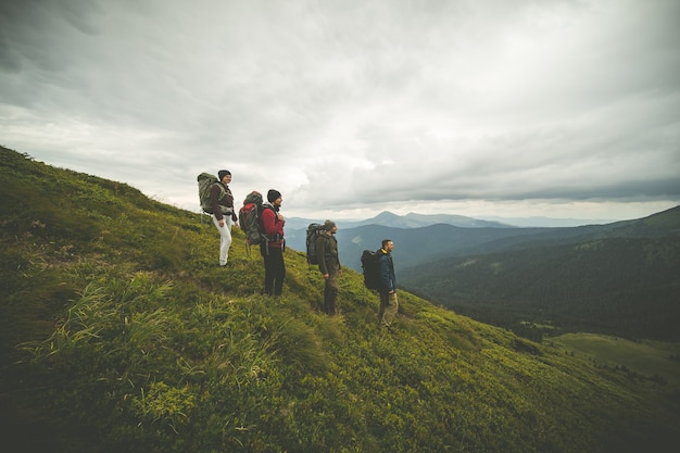 The four hikers with backpacks standing on a mountain