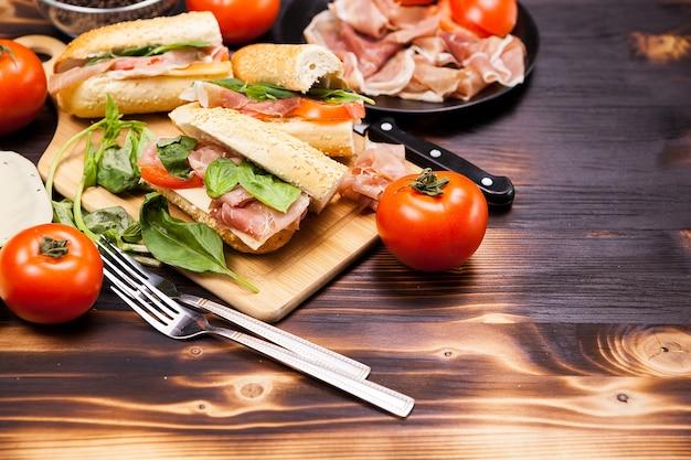 Четыре бутерброда homemande на деревянной доске рядом с ингредиентами, которые были сделаны из