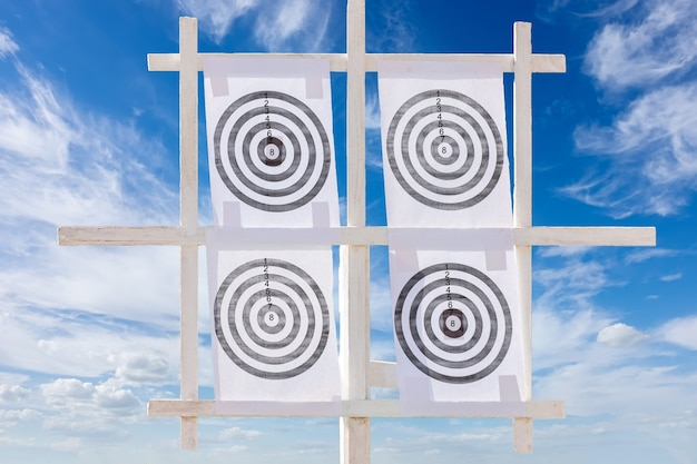 Four icon targets against a blue sky.