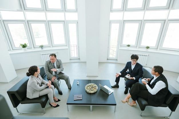 Четыре межкультурных бизнес-партнера сидят на черных кожаных диванах у стола, проводят мозговой штурм и обсуждают новые стратегии в офисе
