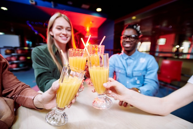 Четверо молодых межкультурных друзей чокаются со свежим апельсиновым соком над столом, проводя время в кафе развлекательного центра
