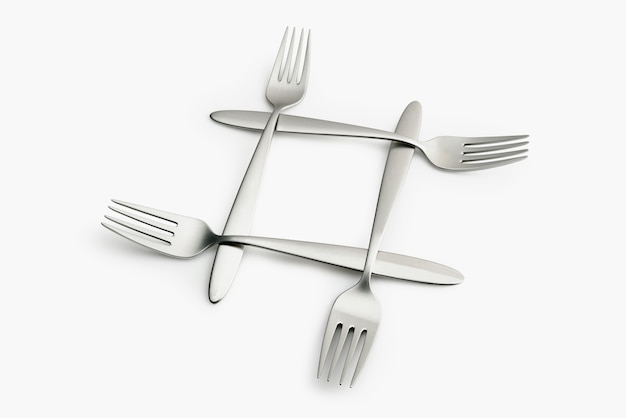 Four interlaced silver forks on white
