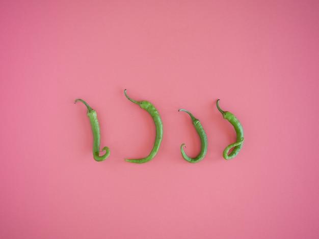 분홍색 벽에 4 개의 고립 된 녹색 곱슬 칠리 페퍼스