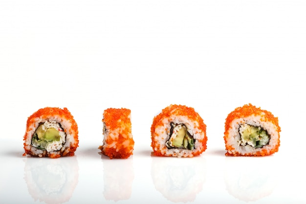 Four japanese maki sushi rolls in a row with flying fish roe, avocado, and cucumber isolated on white