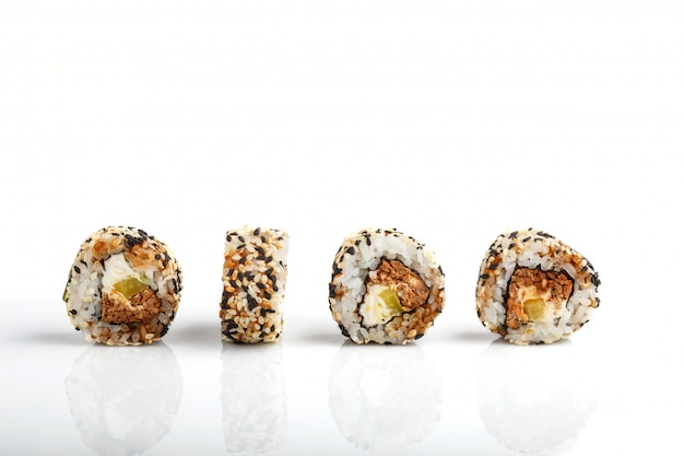 Four japanese maki sushi rolls in a row with salmon, sesame, cucumber and cream cheese isolated on white
