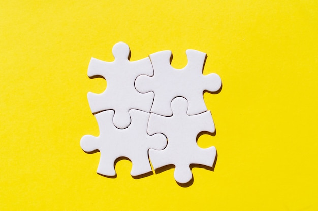 Four jigsaw puzzles pieces on illuminating yellow background