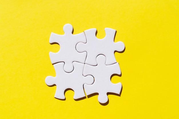 黄色の背景を照らす4つのジグソーパズルのピース