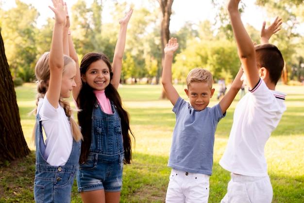 Four joyful friends raising hands up