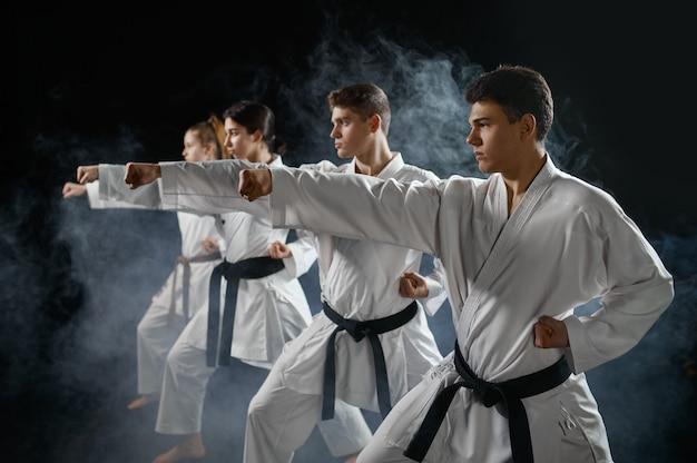 Four karate fighters poses in white kimono, group training. karatekas on workout, martial arts