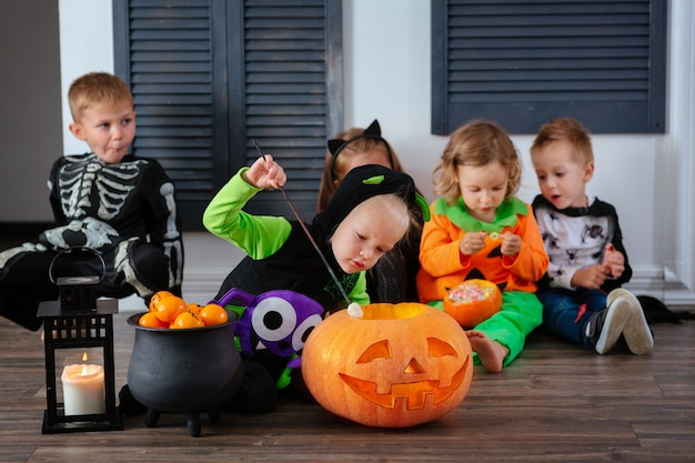 Four kids in carnival costumes are celebrating halloween and fry marshmallows