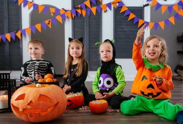 Four kids in carnival costumes are celebrating halloween and playing with pumpkins and candies
