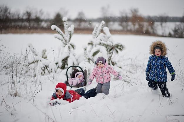 冬の日に楽しんでいる4人の子供。