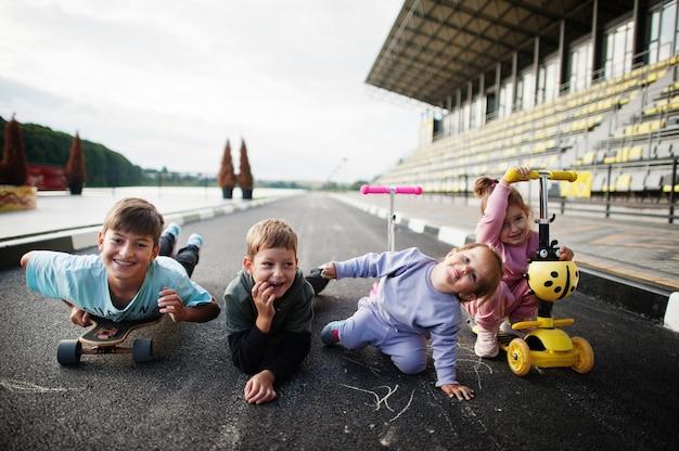 アスファルトで遊んで楽しんでいる4人の子供。スポーツの家族は、スクーターやスケートで屋外で自由な時間を過ごします。 Premium写真