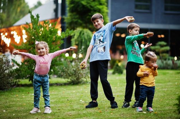 夕方の庭でドーナツを持つ4人の子供。おいしいおいしいドーナツ料理。