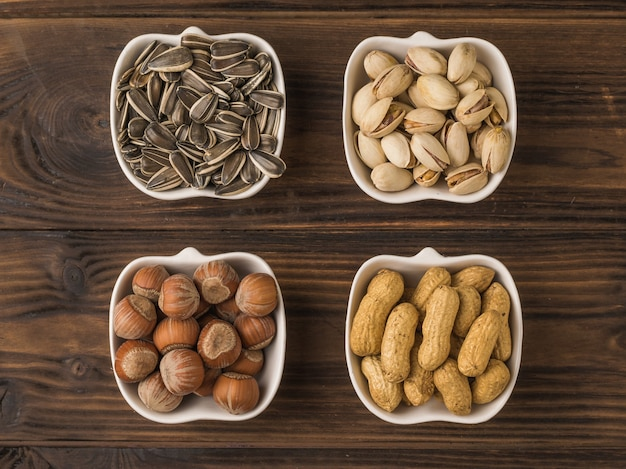 Four kinds of nuts and seeds in white bowls on a wooden table. a mixture of nuts and seeds. flat lay.