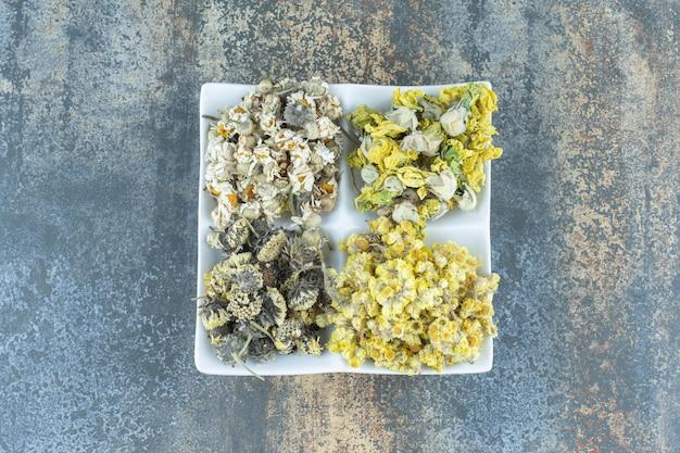 Четыре вида сушеных цветов на белой тарелке.