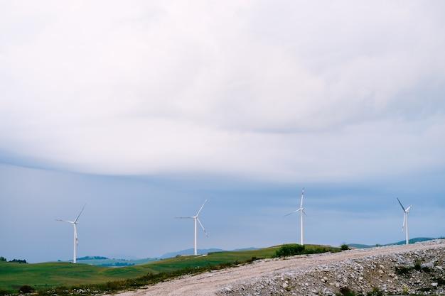 푸른 비 구름에 맞서 수평선에 4 개의 대형 풍력 터빈이 일렬로 서 있습니다.