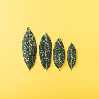 Четыре листа с блеском, расположенные по размеру на желтом фоне плоская рамка осенняя концепция
