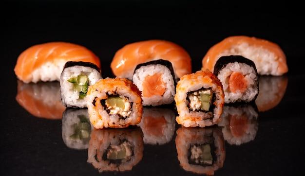 Четыре ролла маки подряд с лососем, авокадо, тунцом и огурцом, изолированные на черном фоне. свежие кусочки хосомаки с рисом и нори. крупный план вкусной японской еды с суши-роллом.