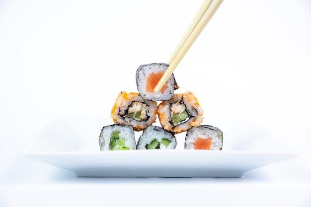 Четыре ролла маки подряд с лососем, авокадо, тунцом и огурцом, изолированные на белом фоне. свежие кусочки хосомаки с рисом и нори. крупный план вкусной японской еды с суши-роллом.