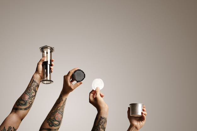 エアロプレスとスペアパーツが白い代替コーヒー醸造コマーシャルで分離された4人の男の手