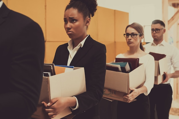Four managers in queue are holding office boxes.