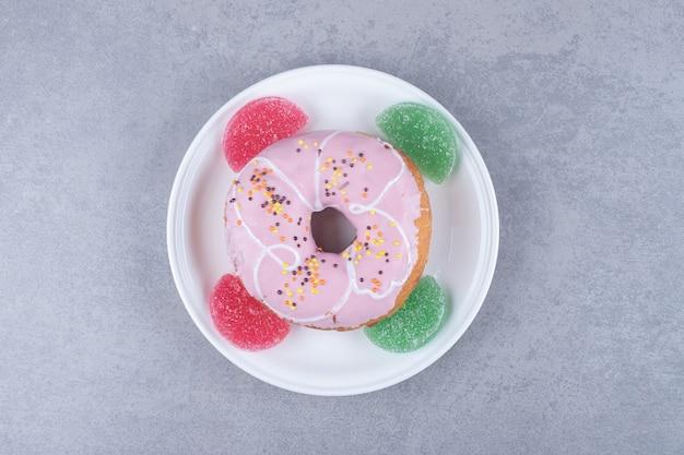Четыре мармелады и пончик на блюде на мраморной поверхности