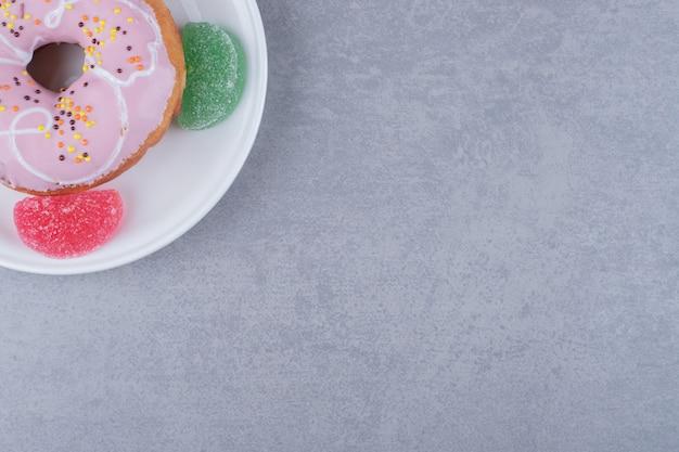 大理石の表面の大皿に4つのマーマレードとドーナツ