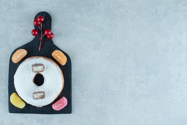 Four marmelades and a donut on a black board on marble.