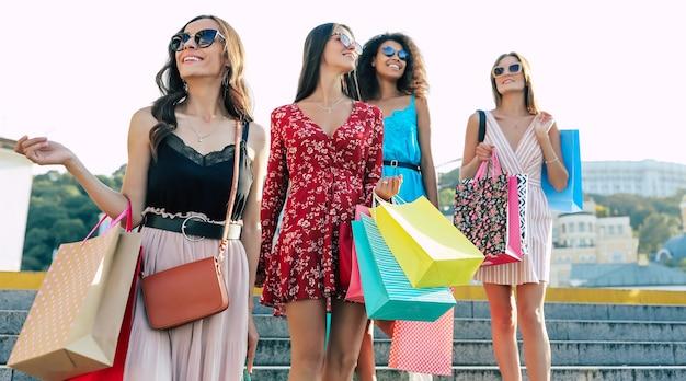 夏の装いをした4人の素晴らしい女性が、市内中心部の路上でポーズをとり、喜びに笑みを浮かべて、購入したものをカメラに見せています。