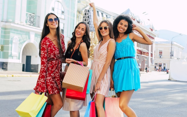 Четыре чудесные женщины в летних нарядах позируют на улице в центре города, радостно улыбаются и демонстрируют свои покупки на камеру.