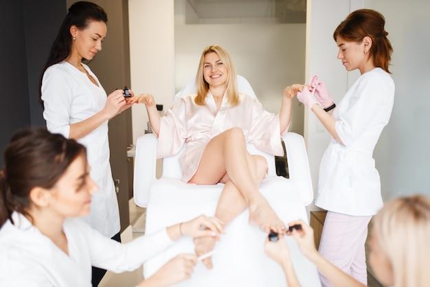 Четыре мастера и одна женщина, процедура педикюра и маникюра в салоне красоты.