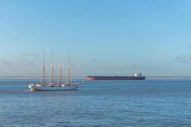Четыре мачты парусное судно и грузовой корабль в море