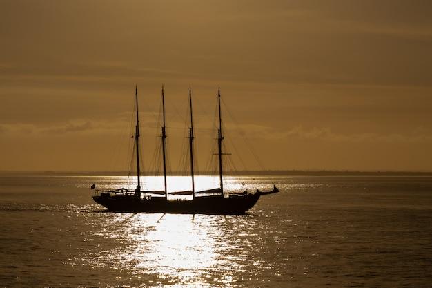 Четыре мачты парусный корабль в море фото, сделанное против солнца