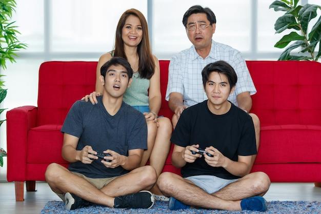 両親と2人の大人の息子で構成される4人のアジア人家族が、ジョイスティックを使用して、休日に自宅の居心地の良いリビングルームで幸せにソファでビデオゲームを楽しんでいます。