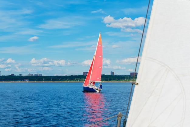 4명의 남자가 해안을 배경으로 호수에 빨간 돛이 달린 범선을 타고 항해하고 있다