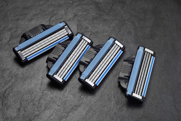 黒のスレートの背景に4つの男性用かみそりの刃が詰め替えられます
