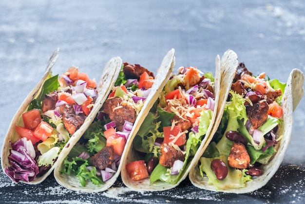 Four mexican tacos on concrete table