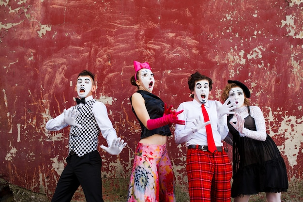Four mimes in fear stand in the background of a red wall.
