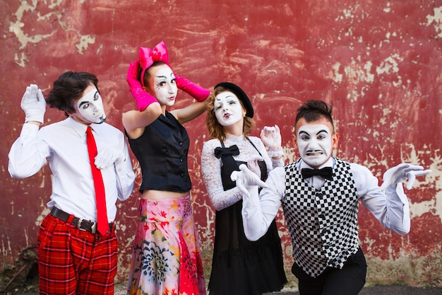 Four mimes standing in a fighting pose on a background of a red wall.