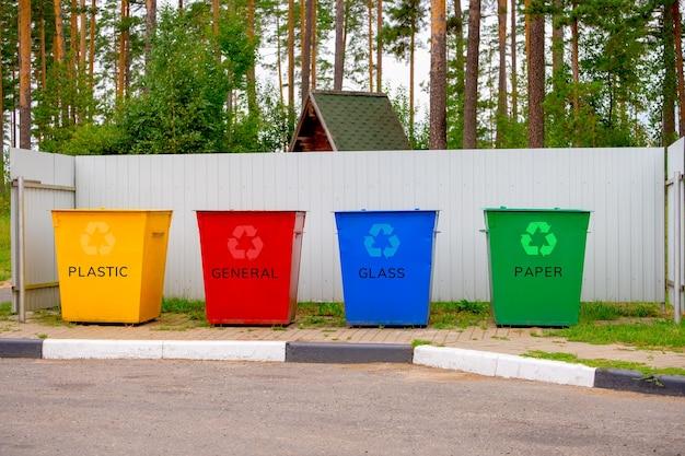 Четыре разноцветных металлических бака с отдельными отходами. забота об окружающей среде и экологии.