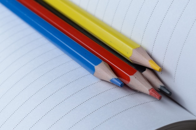4つのマルチカラー鉛筆-青、赤、黄色、黒。開いているノートに横になります。