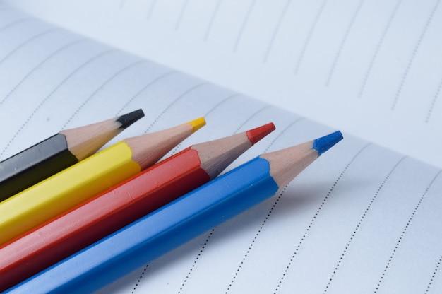 4つのマルチカラー鉛筆-青、赤、黄、黒。開いているノートに横になります。